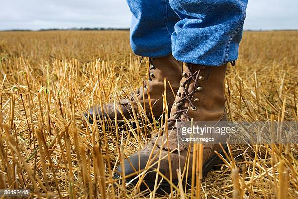 Person wearing work boots in grass field