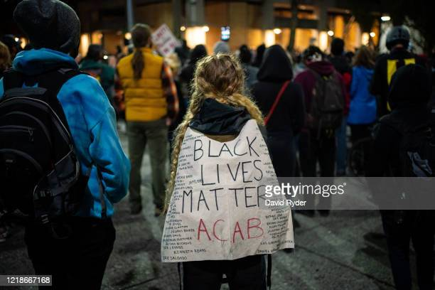 Person wears a Black Lives Matter sign as demonstrators hold a rally and teach-in outside of the Seattle Police Departments East Precinct, which has...