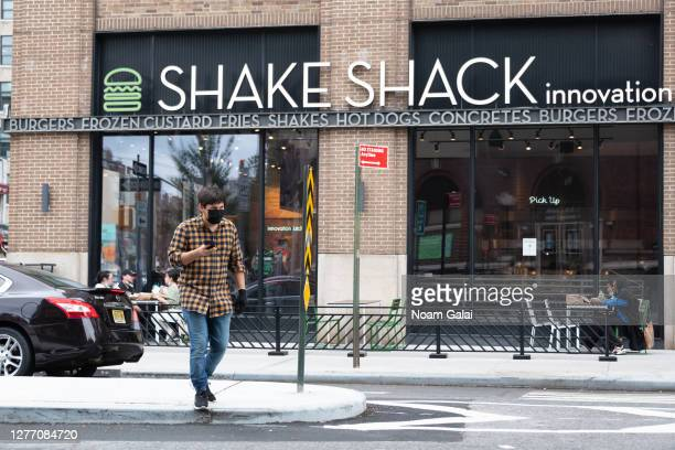 Person wears a face mask outside Shake Shack Innovation Kitchen in Greenwich Village as the city continues Phase 4 of re-opening following...
