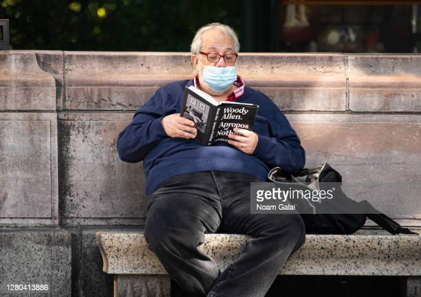 """Person wears a face mask while reading Woody Allen's book """"Apropos of Nothing"""" as the city continues the re-opening efforts following restrictions..."""