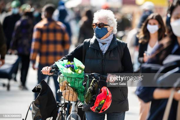 Person wears a face mask while shopping at the Union Square Greenmarket amid the coronavirus pandemic on March 10, 2021 in New York City. It has been...