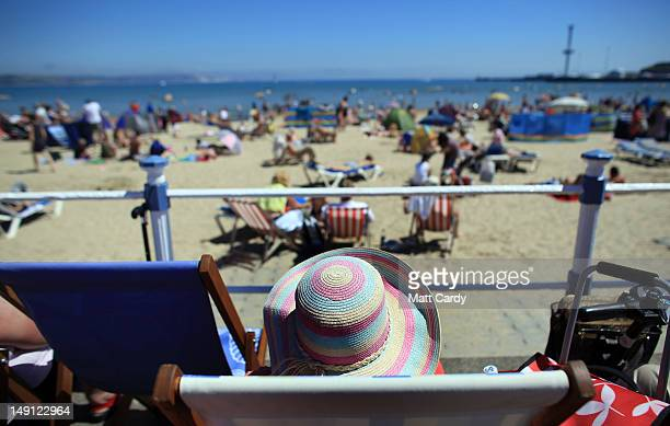 A person wears a hat in the sun as visitors to Weymouth beach spend time in the sunny weather on July 23 2012 in Weymouth England After weeks of wet...