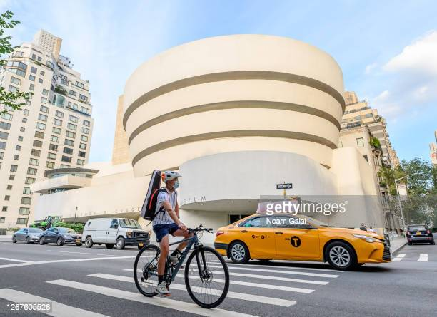 Person wears a protective face mask while riding a bicycle outside Solomon R. Guggenheim Museum as the city continues Phase 4 of re-opening following...