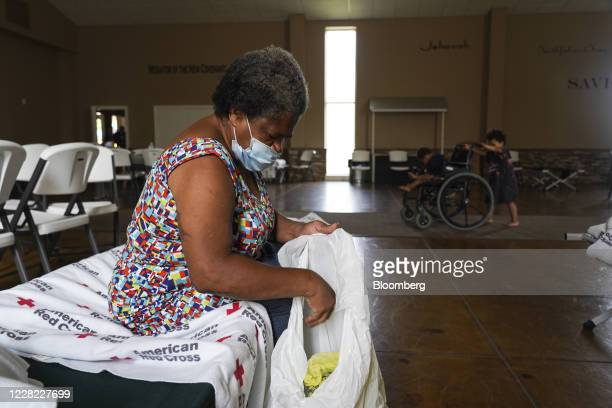 Person wears a protective mask while going through belongings at an evacuation shelter run by the American Red Cross at Cornerstone Baptist Church...
