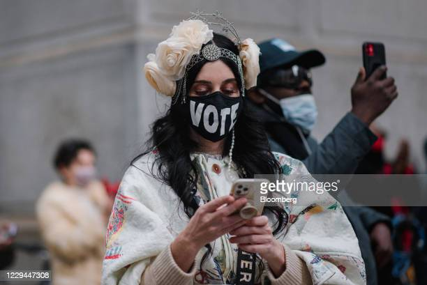 """Person wears a """"Vote"""" protective mask while standing outside Philadelphia City Hall in Philadelphia, Pennsylvania, U.S., on Tuesday, Nov. 3, 2020...."""