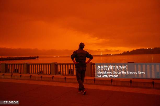 Person who did not want to give his name contemplates the view from Embarcadero as smoky skies from the northern California wildfires casts a reddish...