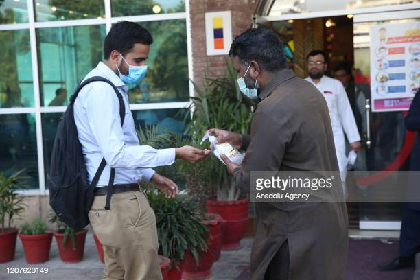 A person who is given hand sanitizer at the entrance of a working place as a precaution against coronavirus is seen in Islamabad Pakistan on March 18...