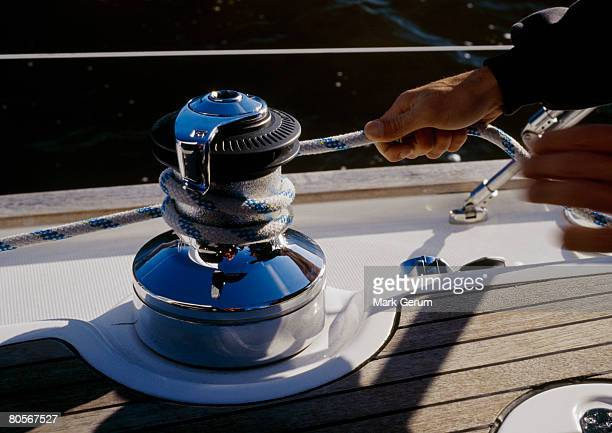 A person winding rope around a crank on a yacht