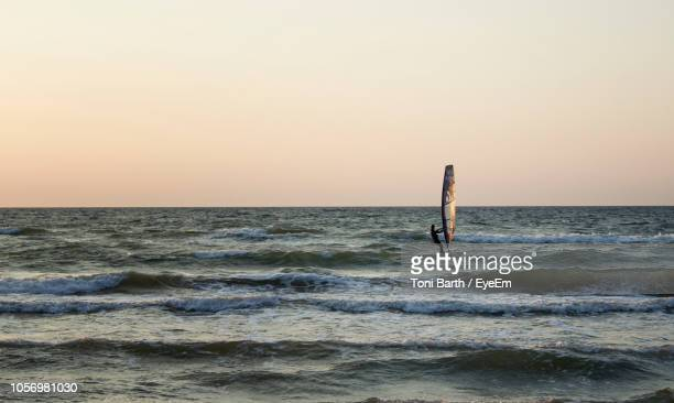 person windsurfing on sea against sky during sunset - mecklenburg vorpommern stock pictures, royalty-free photos & images