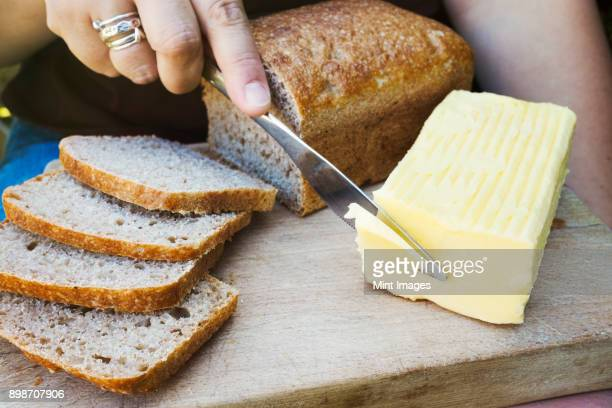 A person with a knife slicing through a block of butter for a sliced bread loaf.