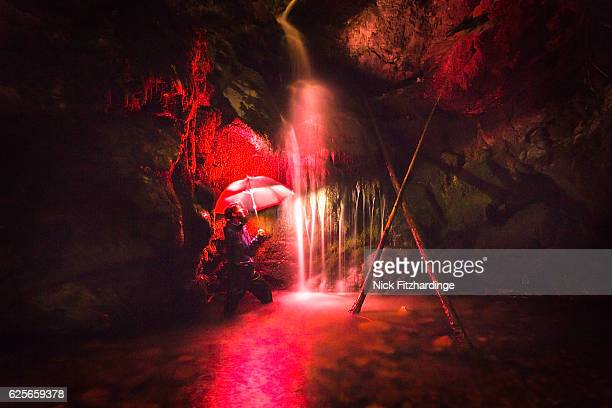 A person with a red umbrella under lower Crawford Falls at night, Okanagan Valley, British Columbia, Canada
