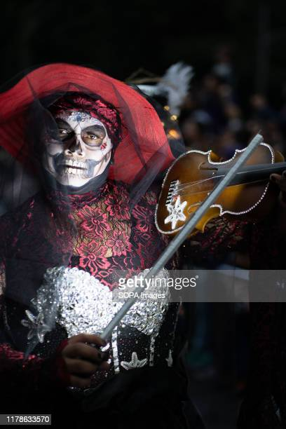 A person with a violin plays to the crowds as part of the procession during the Catrina Festival Thousands of people took to the streets of Mexico...
