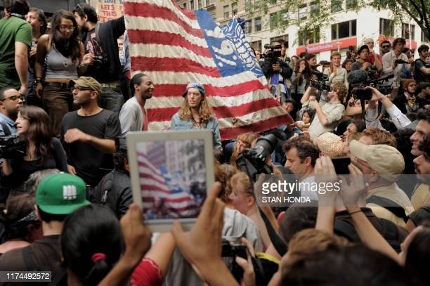 Person with an iPad takes a photograph of a large flag as demonstrators with 'Occupy Wall Street' occupy Zuccotti Park on September 30, 2011 in New...