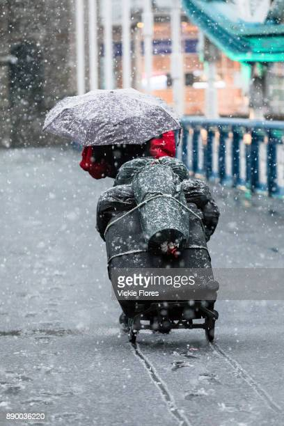 A person with an umbrella suitcase and personal belongings on a trolly walks across Tower Bridge during a heavy snow shower on December 10th 2017...