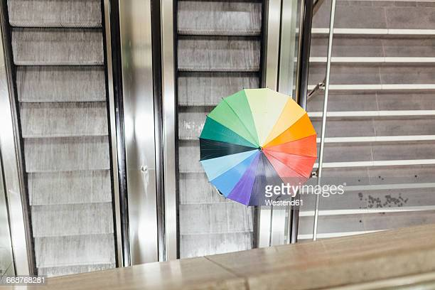 Person with colorful umbrella going up on an escalator, high angle view