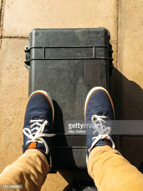 person with feet resting on hard carry case - beige shoe stock pictures, royalty-free photos & images