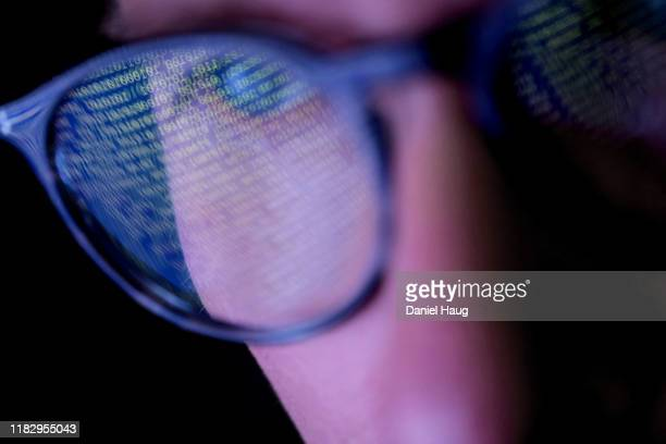 a person with glasses in a dark room looking at computer screen that's displaying codes or programming, with reflections on the glasses keeping the subject engrossed in - data stock pictures, royalty-free photos & images