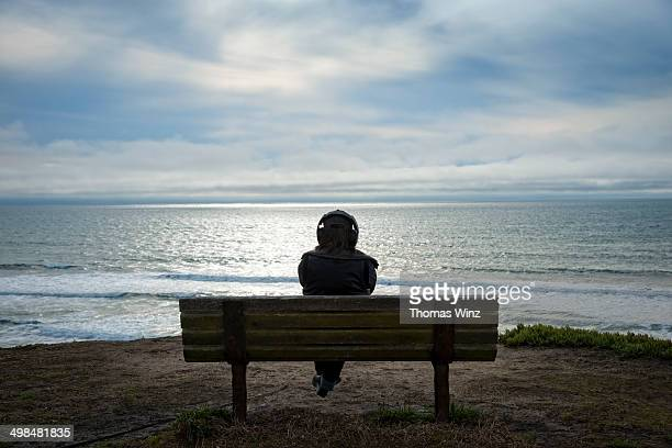 Person with head phones overlooking  Pacific Ocean