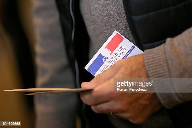 A person with his registration card votes at a polling station on November 20 2016 in Bordeaux France Seven centreright candidates are running in the...