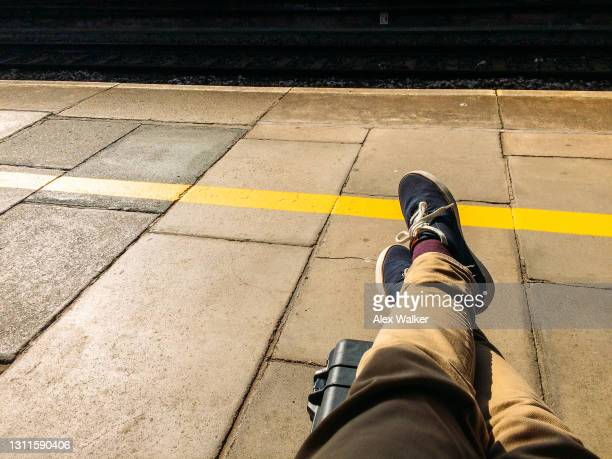 person with legs crossed on station platform - beige shoe stock pictures, royalty-free photos & images