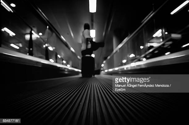 Person With Luggage Standing On Moving Walkway