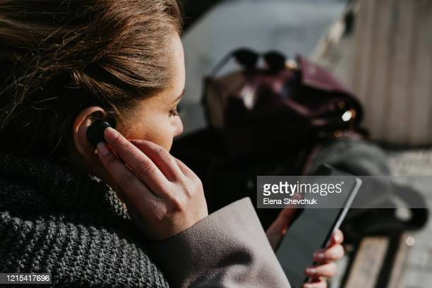 person with mobile phone and bluetooth headset, typing on telephone in the street - ブルートゥース ストックフォトと画像