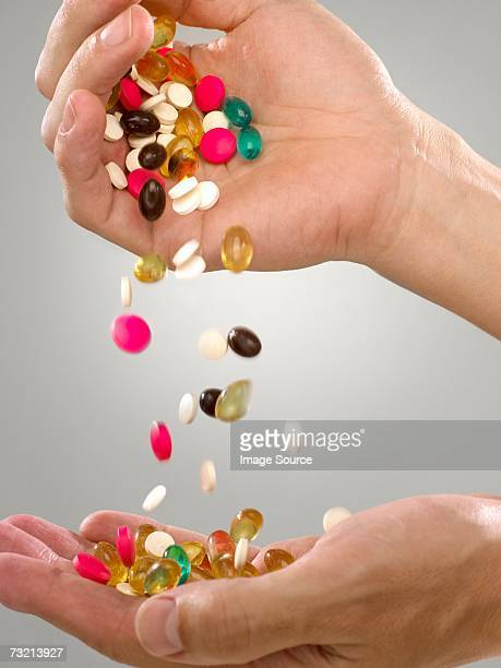 person with pills and capsules - handful stock pictures, royalty-free photos & images