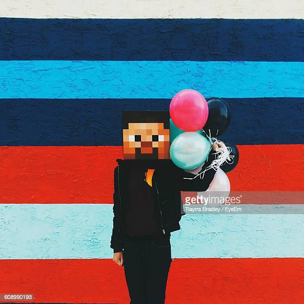 Person With Pixelated Face Holding Balloons Against Striped Wall