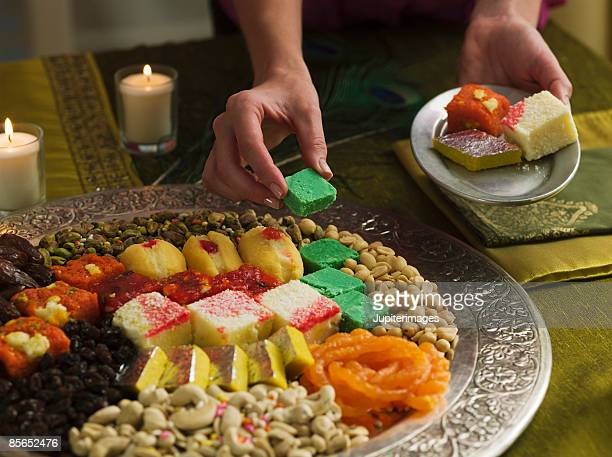 person with platter of diwali sweets - diwali sweets stock photos and pictures