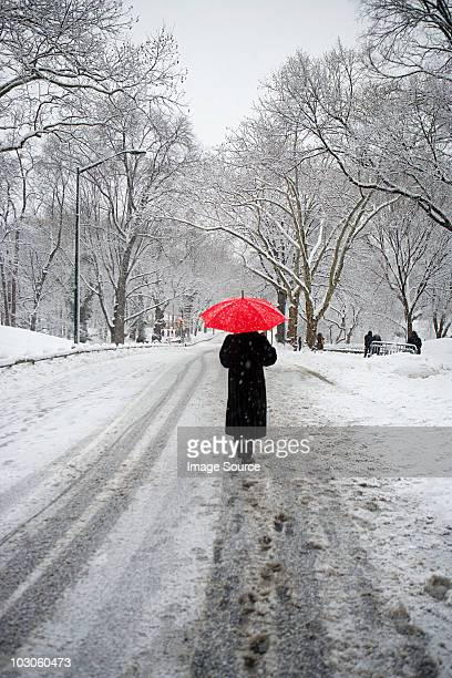 person with red umbrella walking in snow - slush stock photos and pictures
