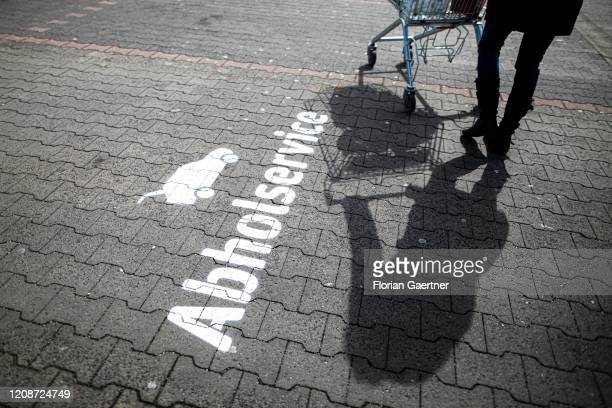 Person with shopping trolley is pictured on a parking space with the sign 'Abholservice' on March 31, 2020 in Niesky, Germany. Many supermarkets...
