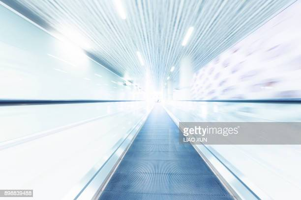 Person with suitcase on a moving escalator