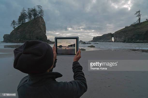 Person with tablet computer on the coast