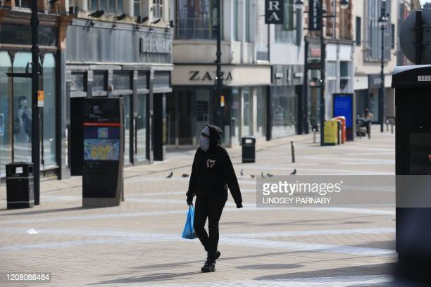 A person with their face covered walks along a city centre shopping street with the shops closed due to coronavirus in Leeds northern England on...