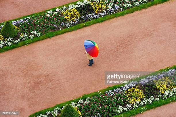 Person with umbrella in rainbow colors on a red gravel path between flower beds in the castle gardens, Fuldaer Stadtschloss City Palace, Fulda, Hesse, Germany