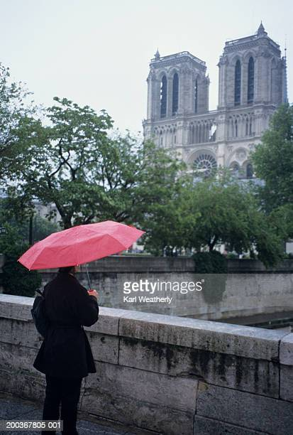 Person with umbrella near Notre-Dame, Paris, France