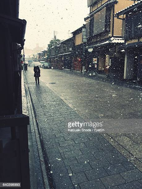 Person With Umbrella Standing On Street Amidst Buildings During Snowfall