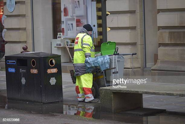 Person, working as a street cleaner, collecting litter from a bin in central Manchester, England, United Kingdom, on Monday 4th January 2015. This...