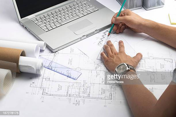 Person working on measurements for a drawing of a building