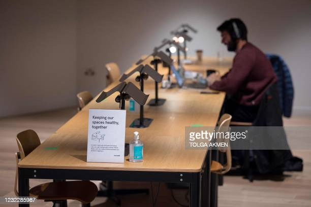 Person works at a shared workspace near signage advising people to maintain social distance at the WeWork, coworking and office space in the City of...