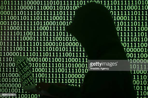 A person works on his computer in front of binary digits in Ankara Turkey on October 29 2017