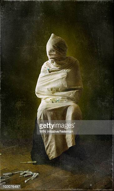 person wrapped in white sheet, syringes on floor - straight jacket stock pictures, royalty-free photos & images