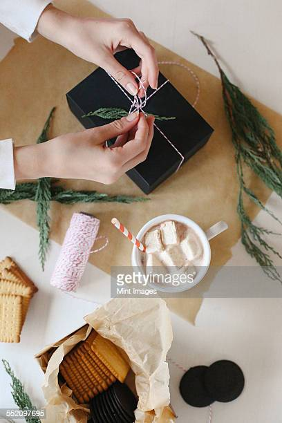 a person wrapping a parcel and a jar of homemade marshmallows. - candy wrapper stock photos and pictures
