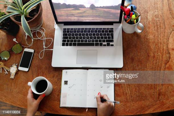 person writing in diary with laptop on desk - home office stock pictures, royalty-free photos & images