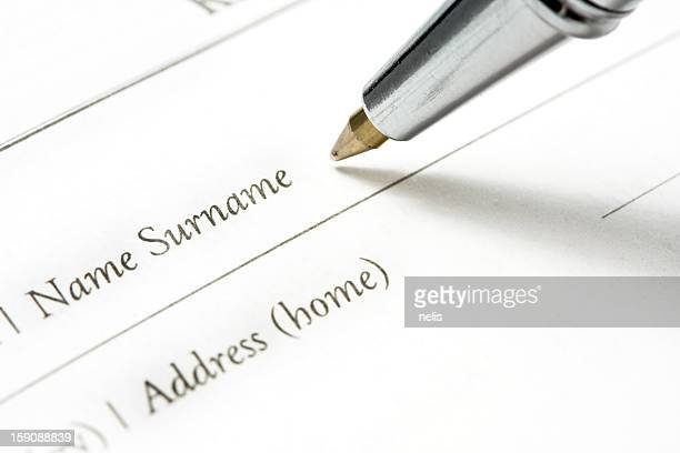 Person writing surname on document