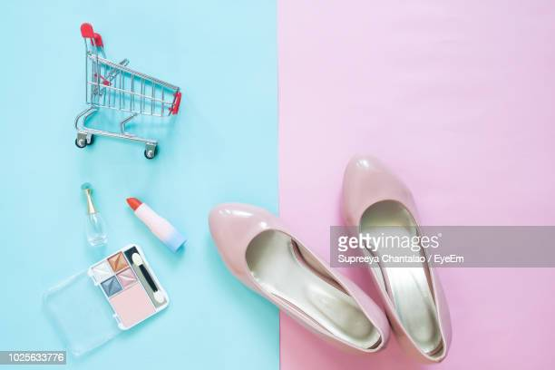 personal accessories and small shopping cart on table - metallic shoe stock pictures, royalty-free photos & images