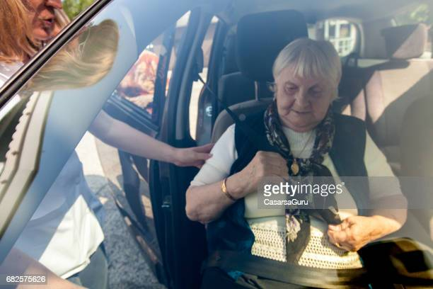 Personal Assistent Helping to Senior Woman into Car