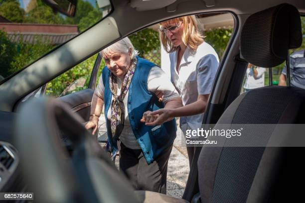 personal assistent helping to senior woman into car - transportation stock pictures, royalty-free photos & images