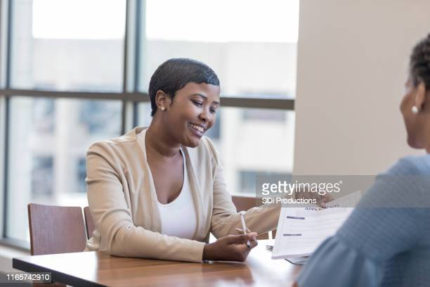 personal banker explains account application to client - cashier stock pictures, royalty-free photos & images