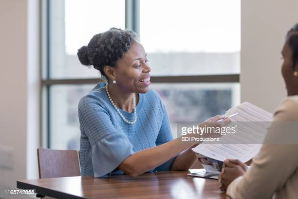 personal banker persuades client to fill out application - american influenced stock photos and pictures
